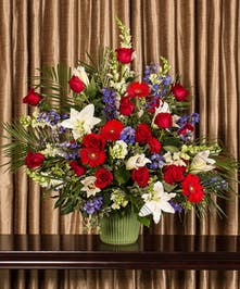 Part of our God Bless America collection, we honor your courageous loved one with our red roses, blue delphinium and fragrant white lilies, standing 24