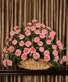 Part of our Best Value collection, send your condolences with style, pink carnations in a handwoven floor basket standing 20