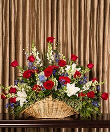 Part of our God Bless America collection, we honor your courageous loved one with our red roses, blue delphinium and fragrant white lilies, measuring 20