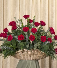 A beautiful display of red Equadorian roses custom created in a handwoven fireside basket.