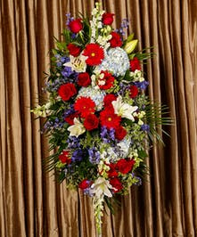Part of our God Bless America collection, we honor your courageous loved one with our red roses, blue delphinium and fragrant white lilies, standing just over 4 feet tall.