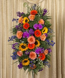 Bright sympathy spray including sunflowers and delphinium stands four feet tall.