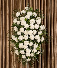 White carnation easle spray, stands on a four foot easle.