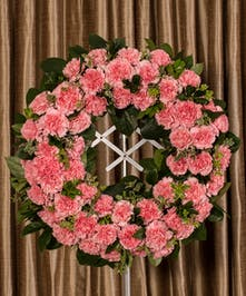 Pink carnation wreath displayed on four foot easle.