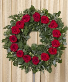 Lush foliage wreath accented with single row of red roses, measures 20