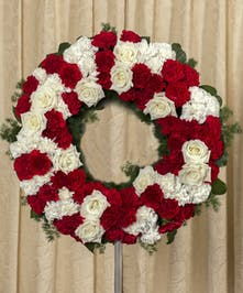 Part of our Rest in Peace grouping, red and white garden flowers designed in a classic wreath tribute, elevated on a four foot stand.