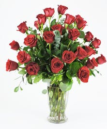 Double dozen red roses displayed with lush foliages in clear vase.