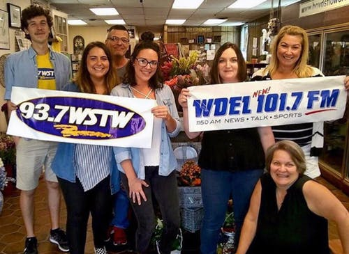 Members of the Boyd's team, posing with banners from several local radio stations