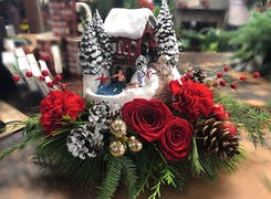 A winter-themed gift, dressed with red roses, pine cones and holly